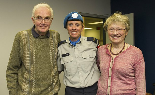 A woman in UN peacekeepers uniform with a man to her left and a woman to her right. They are her parents.