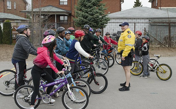 A man in TPS unifrom in front of a large group of children on bicycles