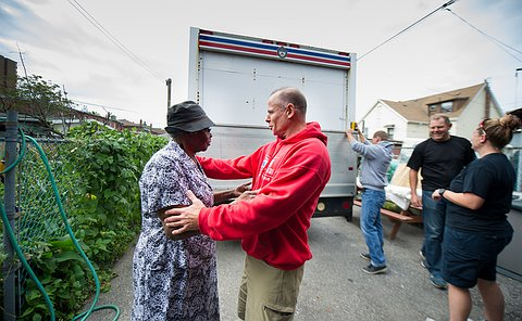 A man with outstretched arms speaks to a woman near a cargo truck
