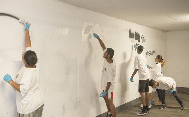 Teenage boys and girls painting a wall white over black spray paint