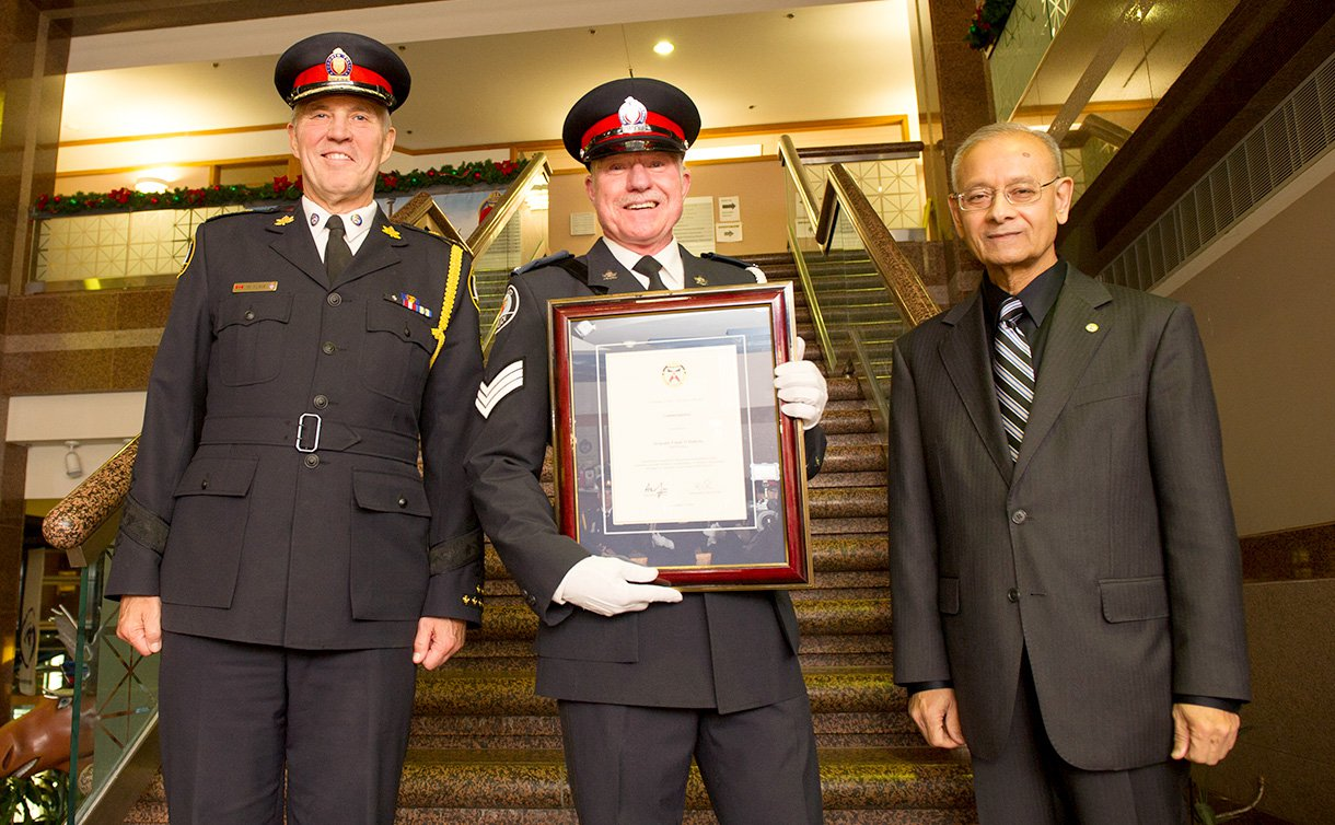 Two men in TPS uniform, one holding a framed certificate, stand beside another man