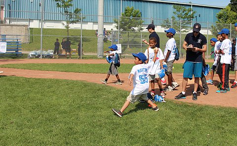 A group of children standing in groups. One throws a ball. A boy in a YIPI uniform with a clipboard stands beside him.