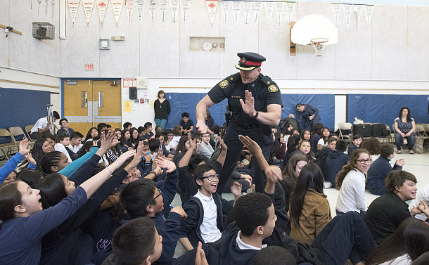 A man in TPS uniform high-fives seated students