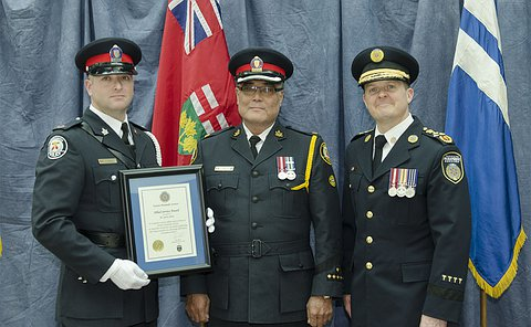 Two men in TPS uniform, one holding a framed certificate and another man in Toronto Paramedic Services uniform stand in front of flags