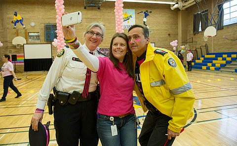 Three people, two in uniform take a selfie.