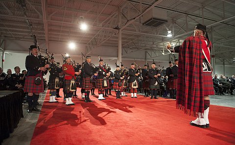 Bagpipers stand on red carpet playing while directed by band leader
