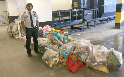 A man in a security uniform by a large amount of toys