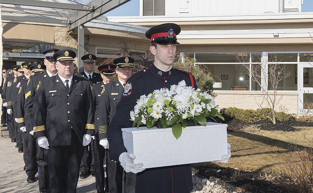 A man in TPS uniform holding a small casket with other men in uniform