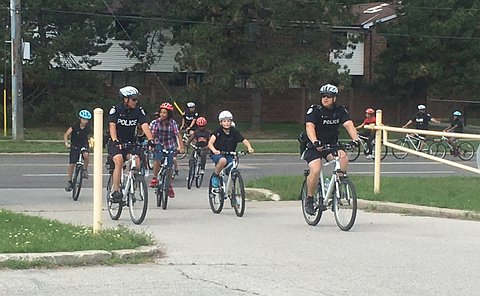 Men in TPS uniform ride bicycles alongside children