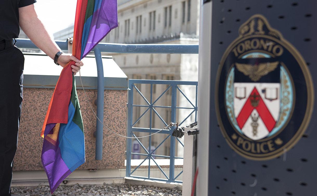 A hand holds a rainbow flag by a TPS podium