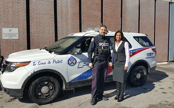 A man in TPS uniform and a woman standing in front of a TPS vehicle