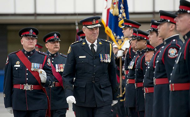 The chief marching as men and women of the ceremonial unit stand for insepction