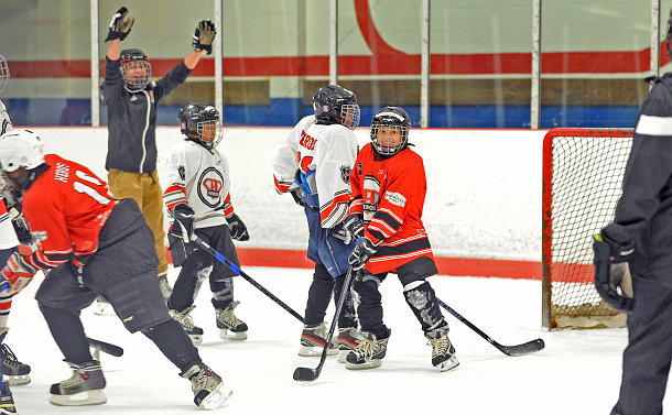 Kids in hockey uniform on ice
