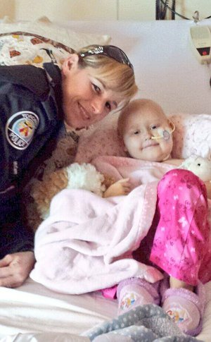 A woman in Toronto police uniform beside a girl in a hospital bed