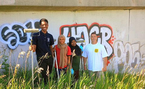 A teenage boy and two girls holding paint rollers next to a man near a concrete structure