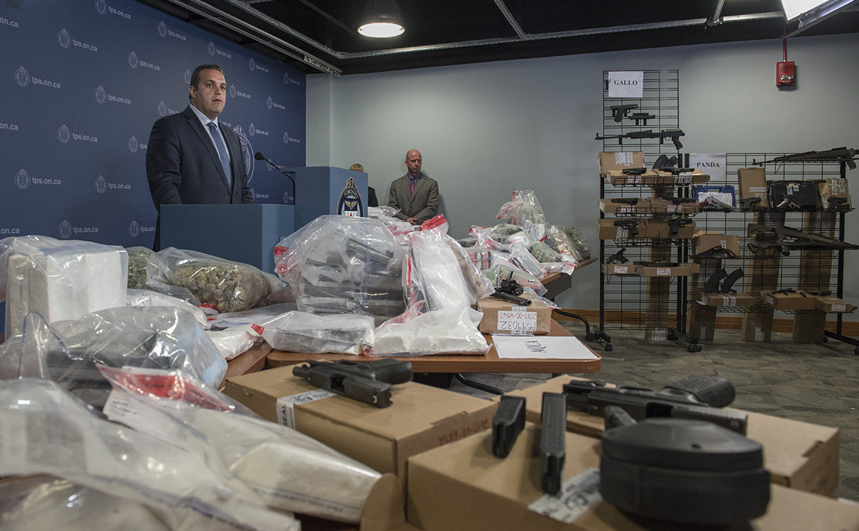 A man at a podium with plastic bags with drugs and cash on tables, handguns and rifles on stand up racks