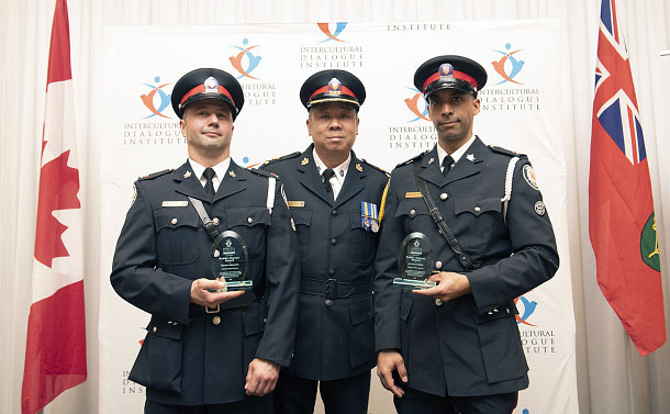 Three men in police uniforms pose while two of them are holding awards