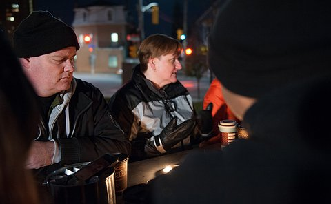 A man is listening intently as the woman next to him speaks. They are wearing coats and sitting outdoors on a bench, it is night-time.