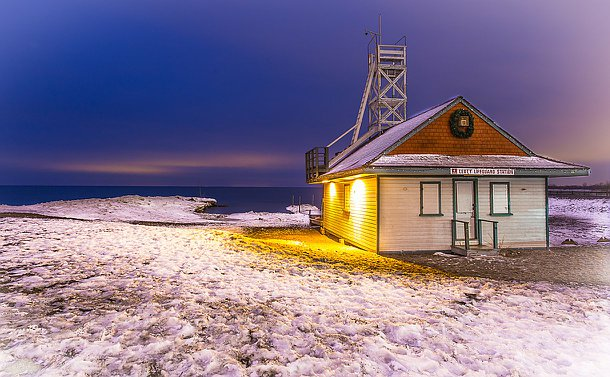 A lifeguard station surrounded by white frozen ground on the edge of a lake
