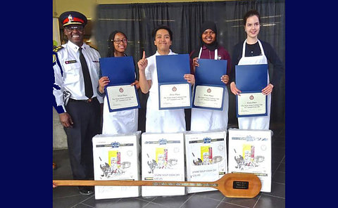 A man in TPS uniform with four teens in aprons holding certificates