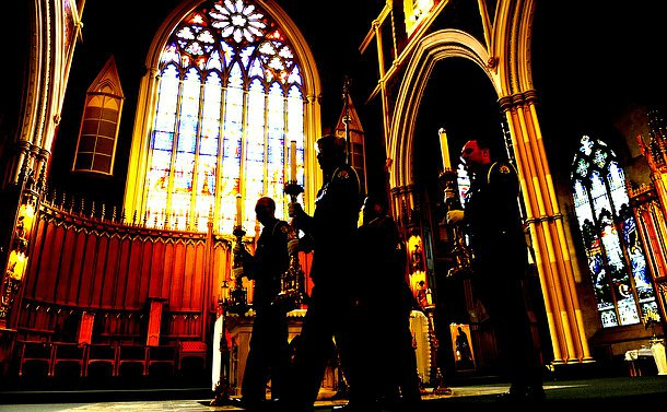 Four people in TPS uniform holding large candles in silhouette against a stained glass window