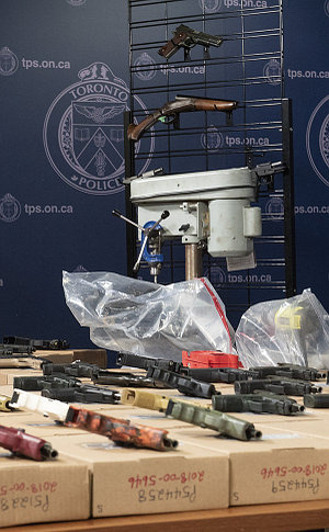guns on a table and rack and a drill press
