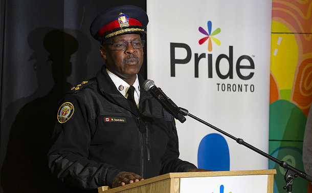 A man in TPS uniform speaks at a microphone