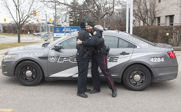 Two men in TPS uniform hugging in front of a scout car