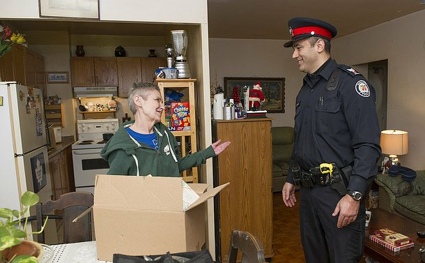 A woman stands in a home with a man in TPS uniform beside a box on a table