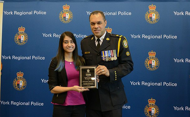 A woman accepts a plaque from a man in TPS uniform against a York Regional Police backdrop