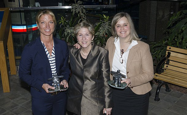 Three women holding statuette awards