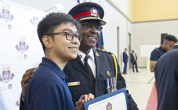 A man in TPS uniform with a teenage boy