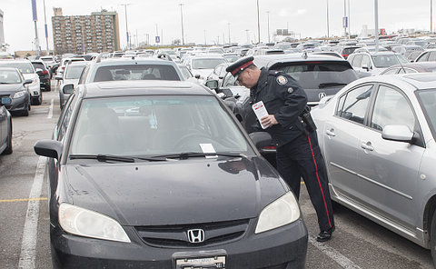 A man in TPS uniform looking into a car in a parking lot