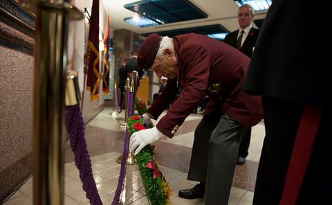 A man in uniform bends to put a wreath in place