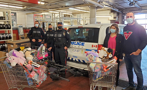 A group of people with a police van of toys