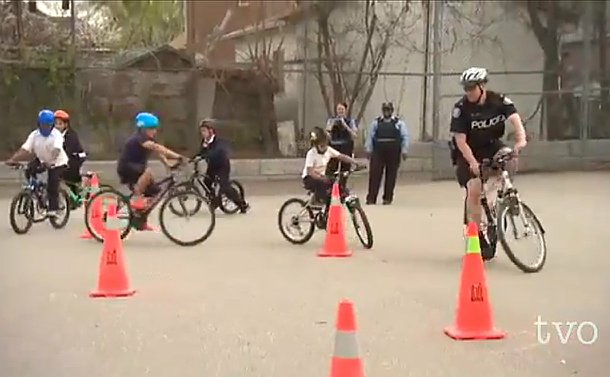 A man in TPS uniform on a bicycle followed by children on bicycles riding through pylons