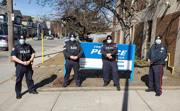 Four men in TPS uniform beside a TPS sign