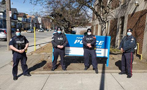 Four men in TPS uniform beside a TPS sign