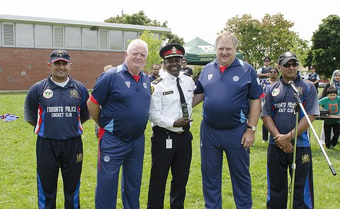 A man in TPS uniform stands with four men in cricket uniform