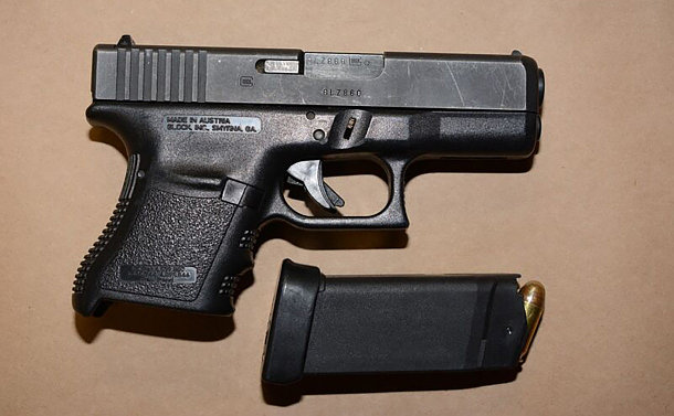 A black handgun on a table with the ammunition clip removed