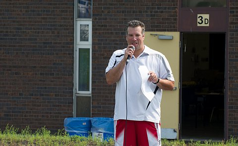 A man in shorts and white tshirt speaks in to a mic.