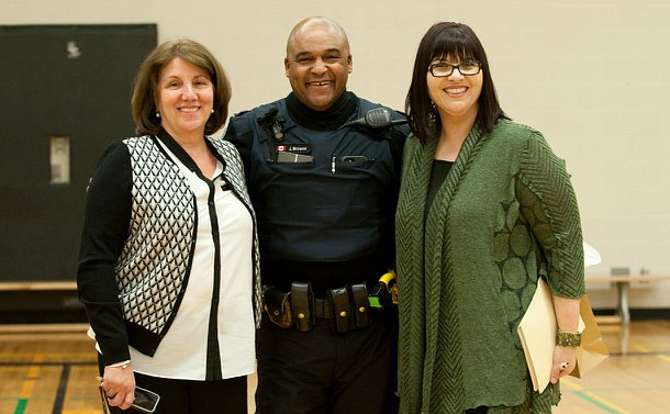 An officer in uniform standing in between two women who are school teachers. Everyone is smiling. They are standing in a school gym.