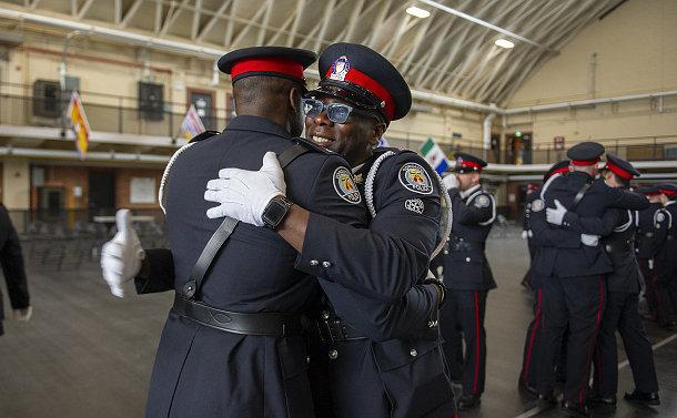 Two men in TPS uniform hugging