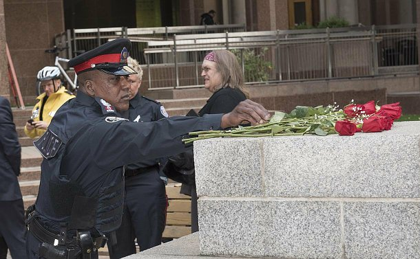 A man in TPS uniform holding a red rose