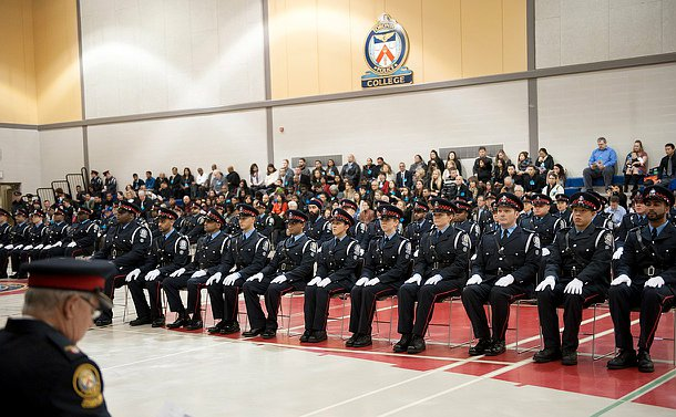 A class in uniform sitting on chairs facing the podium.