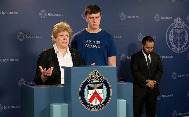 A woman stands beside a podium and a boy and another man