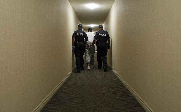 Two police officers hod a man's arms in a hallway