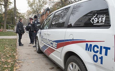 Two men in TPS uniform with a woman by a TPS minivan