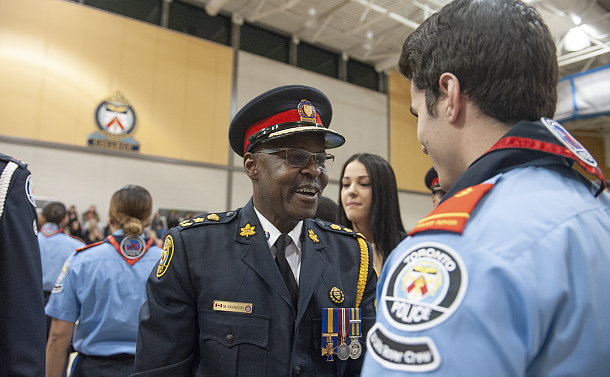 A man in TPS uniform shaking hands with a man in TPS rover uniform