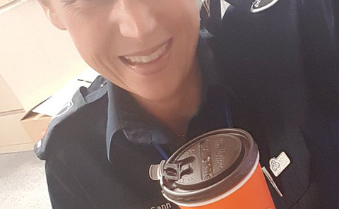 A woman in TPS uniform holding a coffee cup